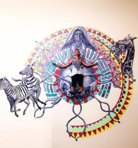 Lindsay Carron stands within a Kenyen inspired artwork with Zebras and a Giraffe on the edges of a circular pattern that she painted in collaboration with fellow artist Ngene Mwaura.