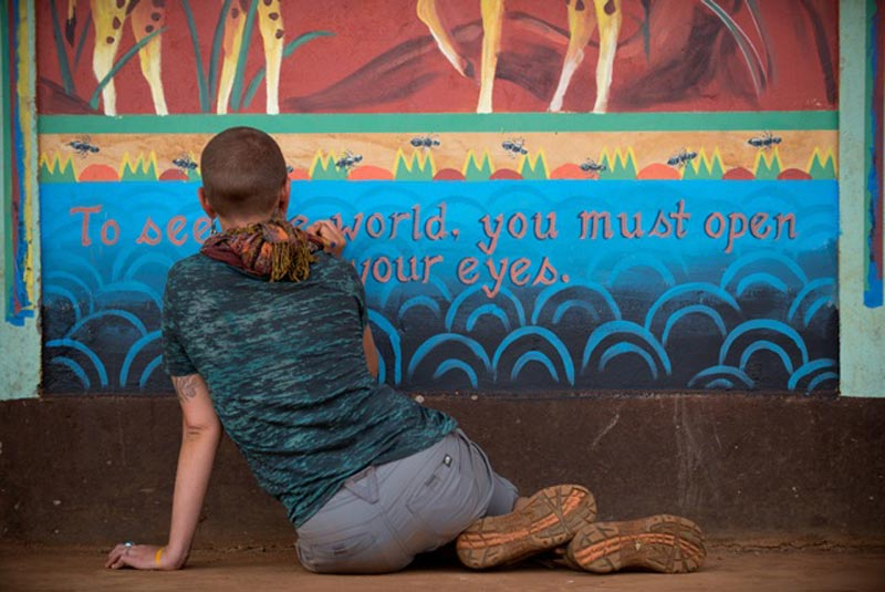 "Lindsay Carron sits on the ground finishing up a mural she painted with team In Relation in a Maasai village in Kenya that reads: ""To see the world, you must open your eyes."""