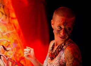 With red light from a piece of her work warming her painted face, Lindsay Carron takes a brief pause from her work during a live painting session.